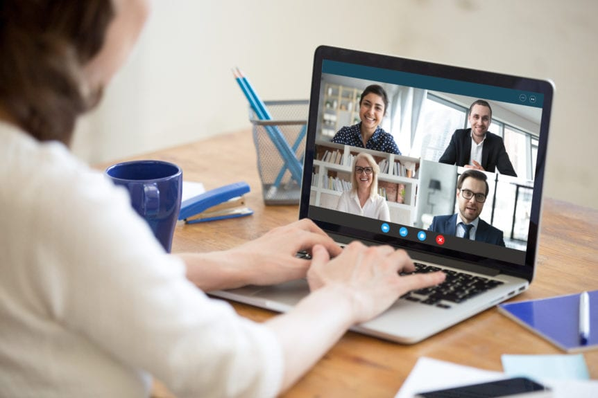 Diverse people take part in group video call pc screen cam app view over woman shoulder, seated at desk. Solve business issues distantly during coronavirus pandemic outbreak, videoconferencing concept